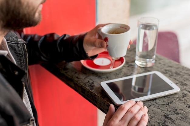 Homme barbu tenant une tasse près d'une tablette