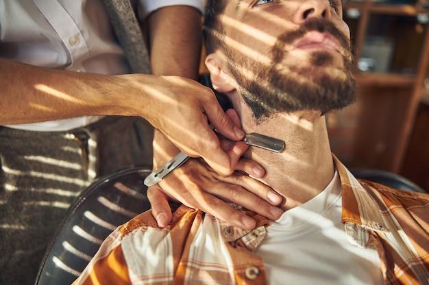 Homme barbu tenant la tête haute pour qu'un coiffeur le rase