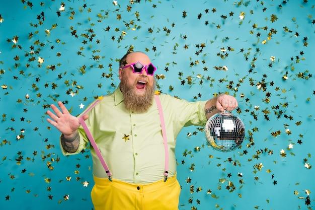 Un homme barbu tient une boule disco sur fond bleu avec une chute de serpentine
