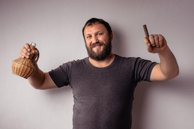 L'homme barbu tient une bouteille d'alcool et de cigare et fait la fête.