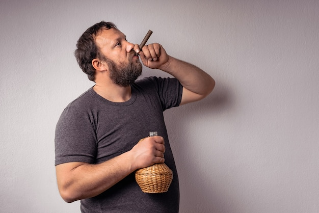 L'homme barbu tient une bouteille d'alcool et fume son cigare et célèbre.