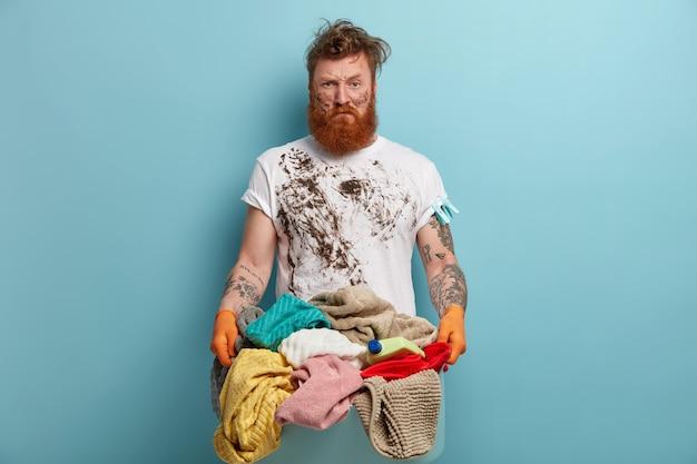 Un homme barbu tient un panier à linge, submergé par les tâches ménagères
