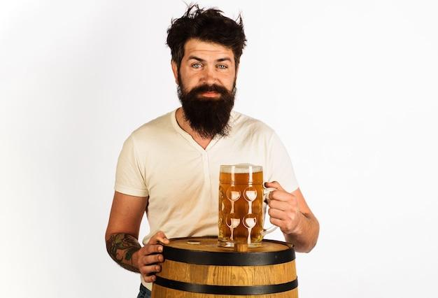 Homme barbu avec tonneau en bois et verre de bière. oktoberfest, boisson, alcool.