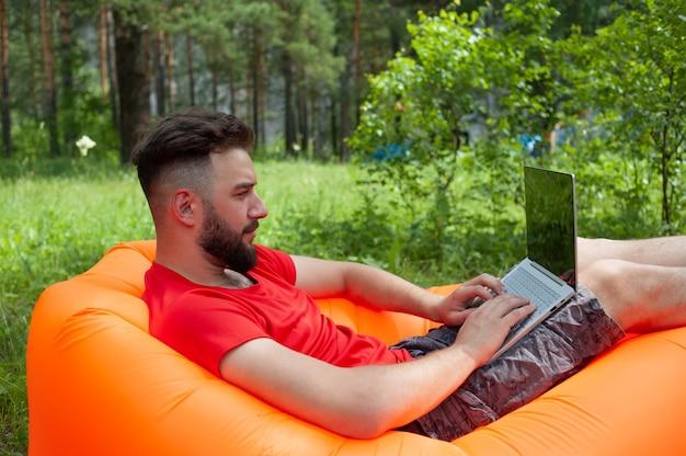 Homme barbu travaille et souriant avec un ordinateur portable dans le parc sous l'arbre. heureux pigiste est
