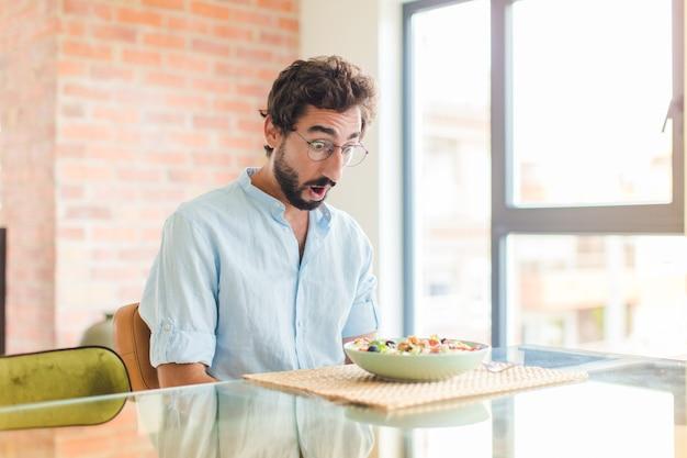 Homme barbu à très choqué ou surpris, regardant la bouche ouverte en disant wow