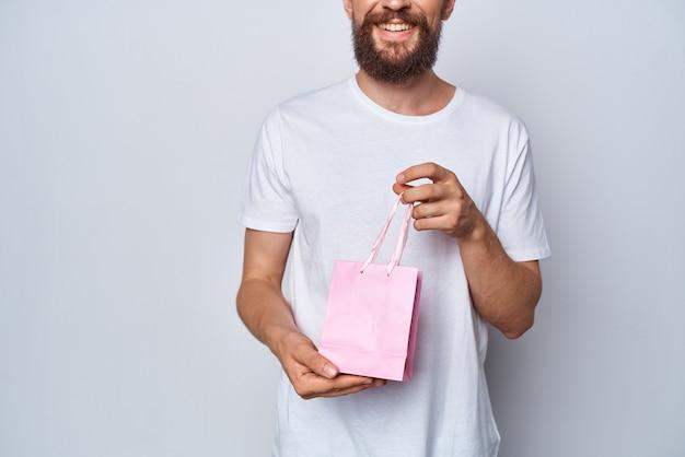 Homme barbu en tshirt blanc paquet rose cadeau pour studio femme