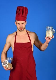 Homme barbu en uniforme de cuisinier. cuisine et concept culinaire professionnel. concept de préparation des aliments et d'ustensiles de cuisine. cook tient des bocaux avec des céréales.