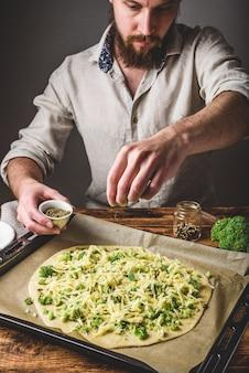 L'homme barbu verse des épices sur une pizza avec du brocoli, de la sauce pesto et du fromage