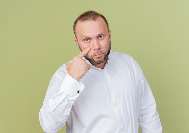 Homme barbu vêtu d'une chemise blanche pointant avec l'index sur son œil en vous regardant geste debout sur un mur léger