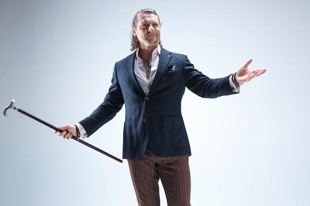 L'homme barde mature en costume tenant une canne.
