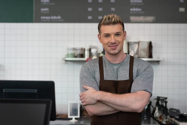Homme barista bras croisés debout derrière une machine à café au café