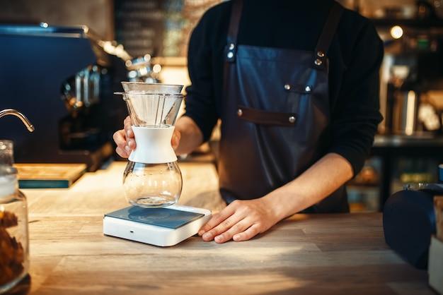 Homme barista met un verre d'eau sur la cuisinière