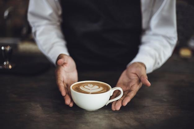 Homme barista préparant un café pour le client dans un café. propriétaire de café servant un client au café.