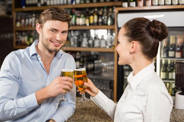 Homme et barmaid portant des bières