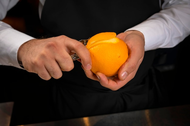Homme barman éplucher une orange