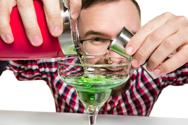 Homme barman expert fait un cocktail à isolé sur un mur blanc.