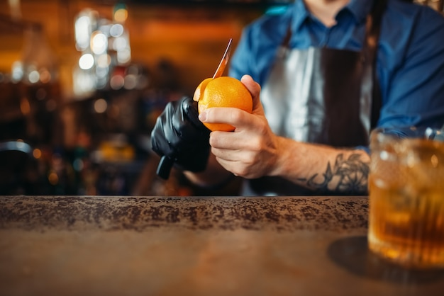 Homme barman nettoie l'orange au comptoir du bar