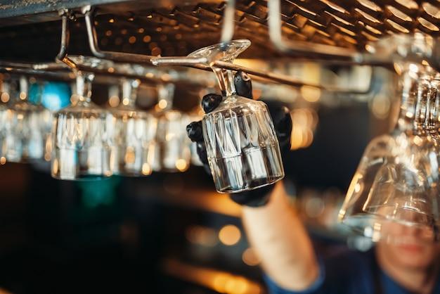 Homme barman prend du verre propre du comptoir du bar