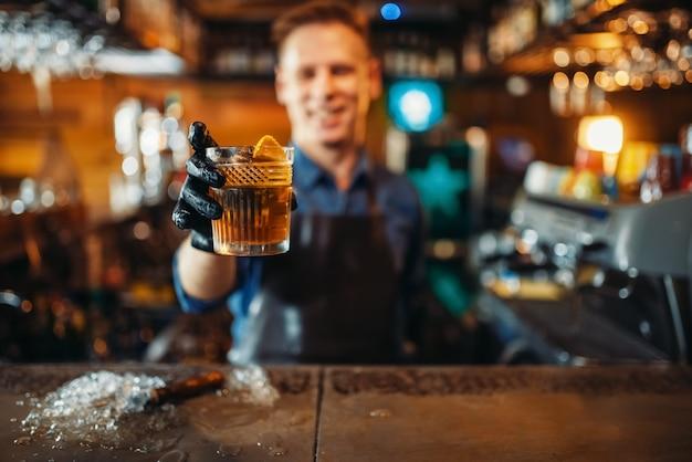 Homme barman présente une boisson alcoolisée fraîche