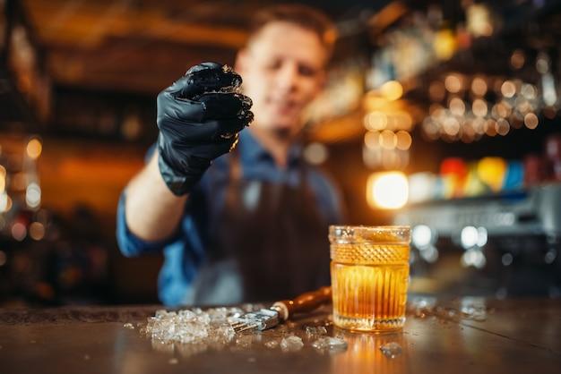 Homme barman travaille avec de la glace au comptoir du bar