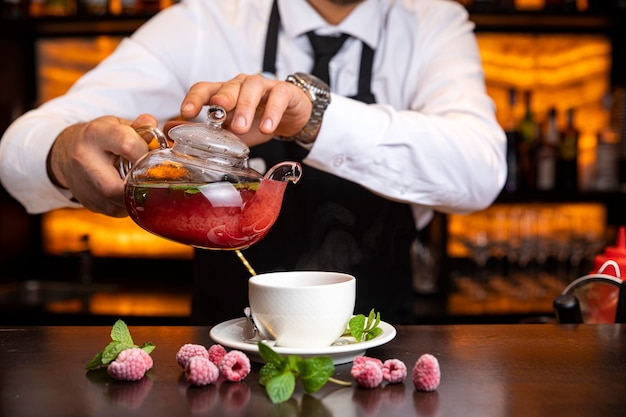 Homme barman verse du thé chaud au bar dans un restaurant