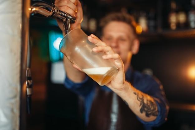 Homme barman verser de la bière au comptoir du bar