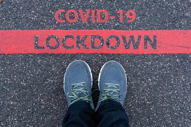 Homme en baskets debout à côté d'une ligne rouge avec texte covid-19 lockdown, concept d'avertissement de restriction ou de sécurité