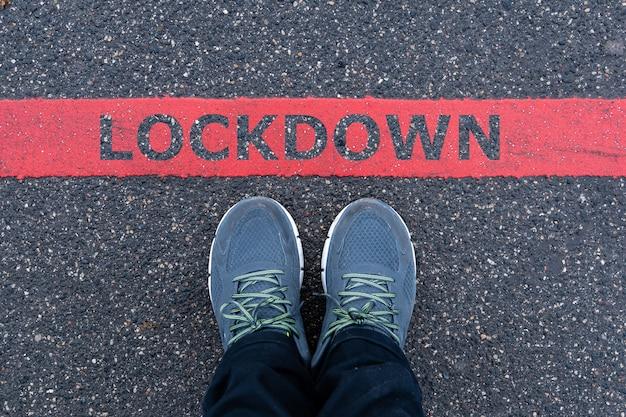 Homme en baskets debout à côté d'une ligne rouge avec texte lockdown, restriction ou concept d'avertissement de sécurité