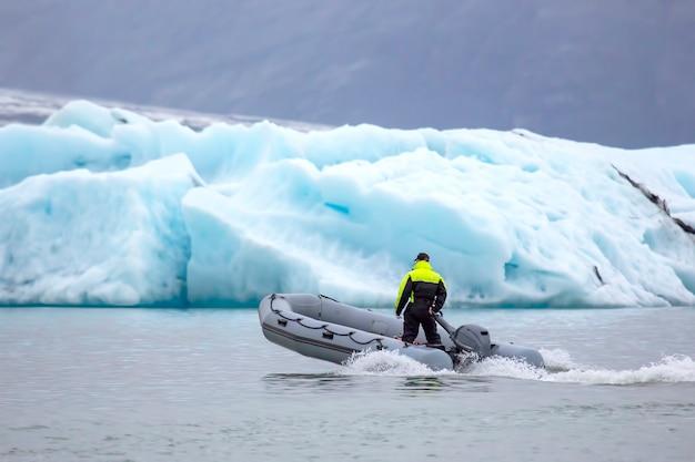 Homme sur un bateau à moteur rapide naviguant sur une lagune glaciaire en islande