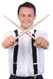 Homme batteur jouant de la batterie et tenant des bâtons.