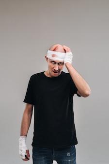 Un homme battu et battu dans un t-shirt noir se dresse sur un fond gris, tenant sa tête douloureuse avec ses mains enroulées autour.