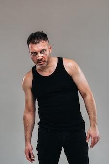Un homme battu dans un t-shirt noir qui ressemble à un toxicomane et un ivre se dresse sur un fond gris.