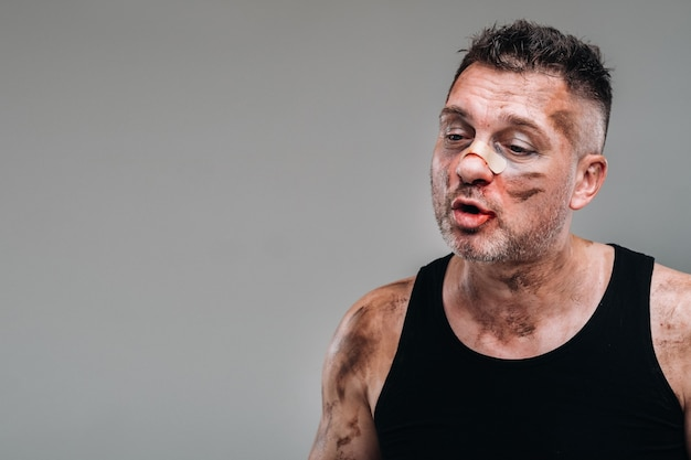 Un homme battu dans un t-shirt noir qui ressemble à un toxicomane et un ivrogne se dresse sur un fond gris