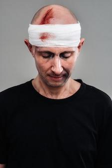 Homme battu dans un t-shirt noir avec sa tête enveloppée dans un bandage.