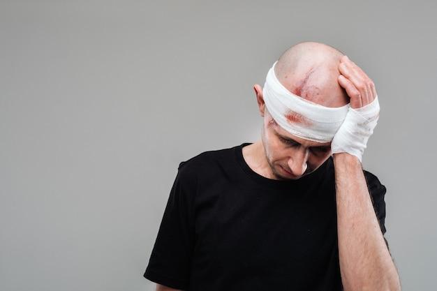 Un homme battu dans un t-shirt noir se dresse contre un mur gris, tenant sa tête douloureuse avec ses mains enroulées autour d'elle