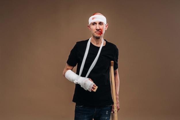Homme battu avec une tête bandée et un plâtre sur son bras se dresse sur des béquilles