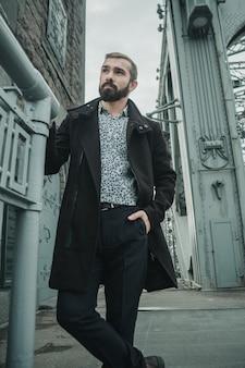 Homme beau et bien habillé avec la barbe posant seul sur la construction du pont et regardant de côté avec sa main dans une poche.