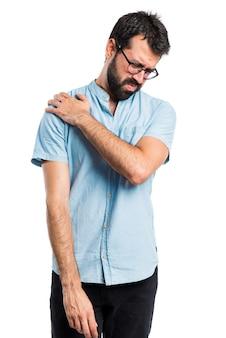 Homme beau avec des lunettes bleues avec douleur à l'épaule