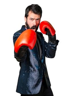 Homme beau avec une veste en paillette avec des gants de boxe