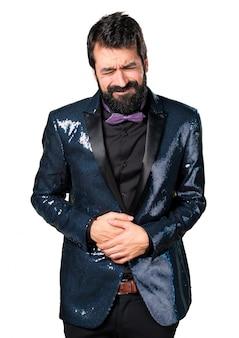 Homme beau avec une veste en paillette avec mal au ventre