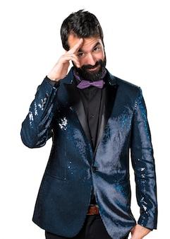 Un homme beau avec une veste en paillette saluant