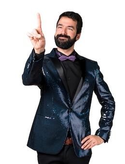 Homme beau avec une veste en paillette touchant un écran transparent