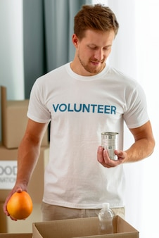 Homme bénévole aidant avec des dons de nourriture
