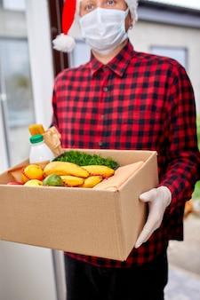 Homme bénévole en bonnet de noel et masque de protection et boîte de don de livraison de gants à la maison dans le courrier des vacances de noël avec boîte d'emballage avec livraison sans contact alimentaire service de quarantaine coronavirus