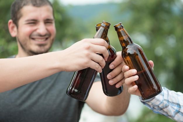 Homme biberon avec des amis dans la nature