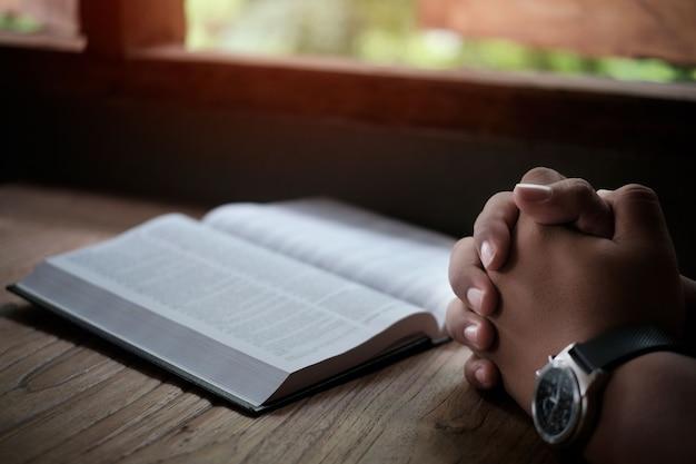 Homme avec la bible en prière, les mains jointes sur sa bible sur une table en bois.