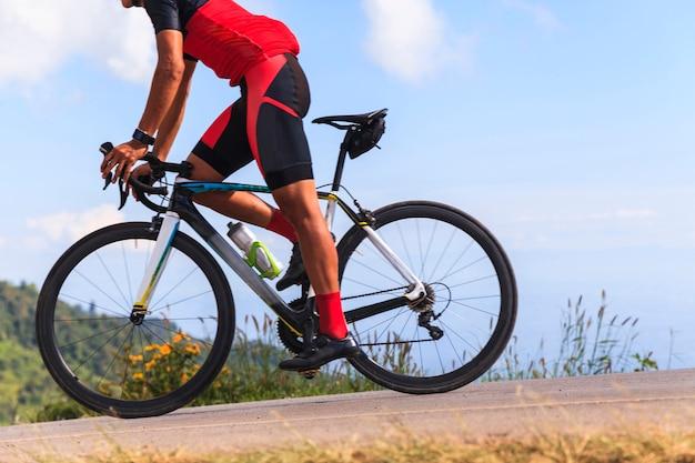Homme à bicyclette sur une route entre les belles montagnes