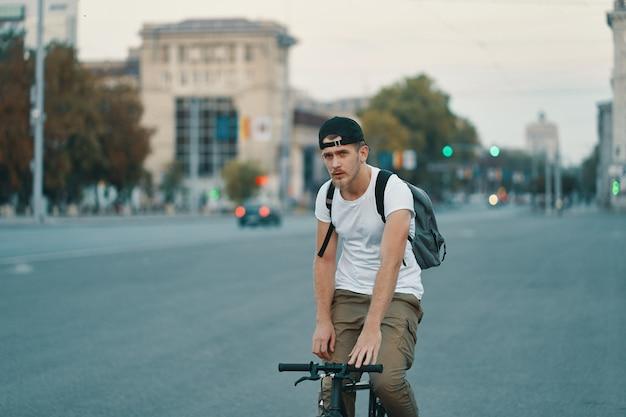 Homme, bicyclette voyageant, dans, urbain, ville, tenant mains, sur, guidon