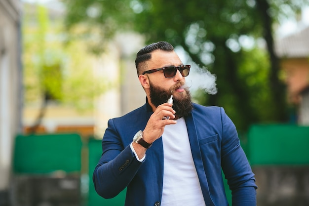 Homme bien habillé fumant une cigarette électronique
