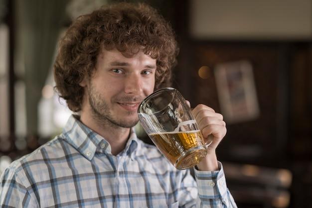 Homme avec de la bière en regardant la caméra